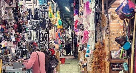 سوق زنقة الستات وفي الصورة تظهر المحلات وامرأة تشتري