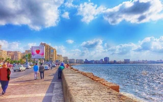 كورنيش الإسكندرية وبعض المارة والجالسين عليه مع مشهد البحر المنعش