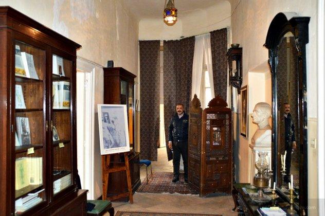 متحف كفافيس من الداخل، في الصورة شخص ومكتبة ولوحة للرسم، رأس تمثال للشاعر اليوناني كفافيس